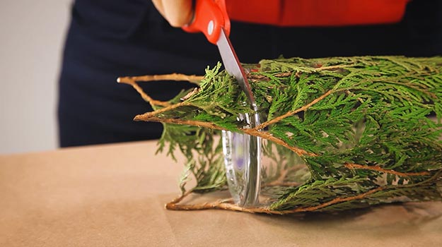 Cut the branches that stick out from the base of the vase with scissors.