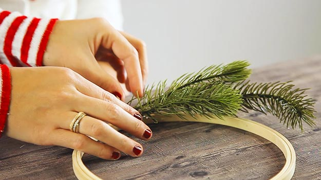 Glue a small fir tree branch onto the hoop with hot glue.