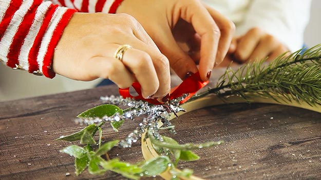 Make a pretty knot with the ribbon and glue it in between your decorative branches.