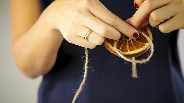Insert the rope and make a new knot to keep the orange in place.